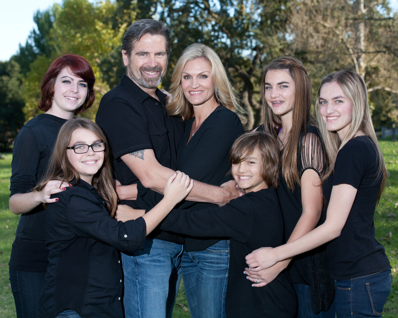 family portrait mom dad 4 girls 1 boy black shirts blue jeans park background