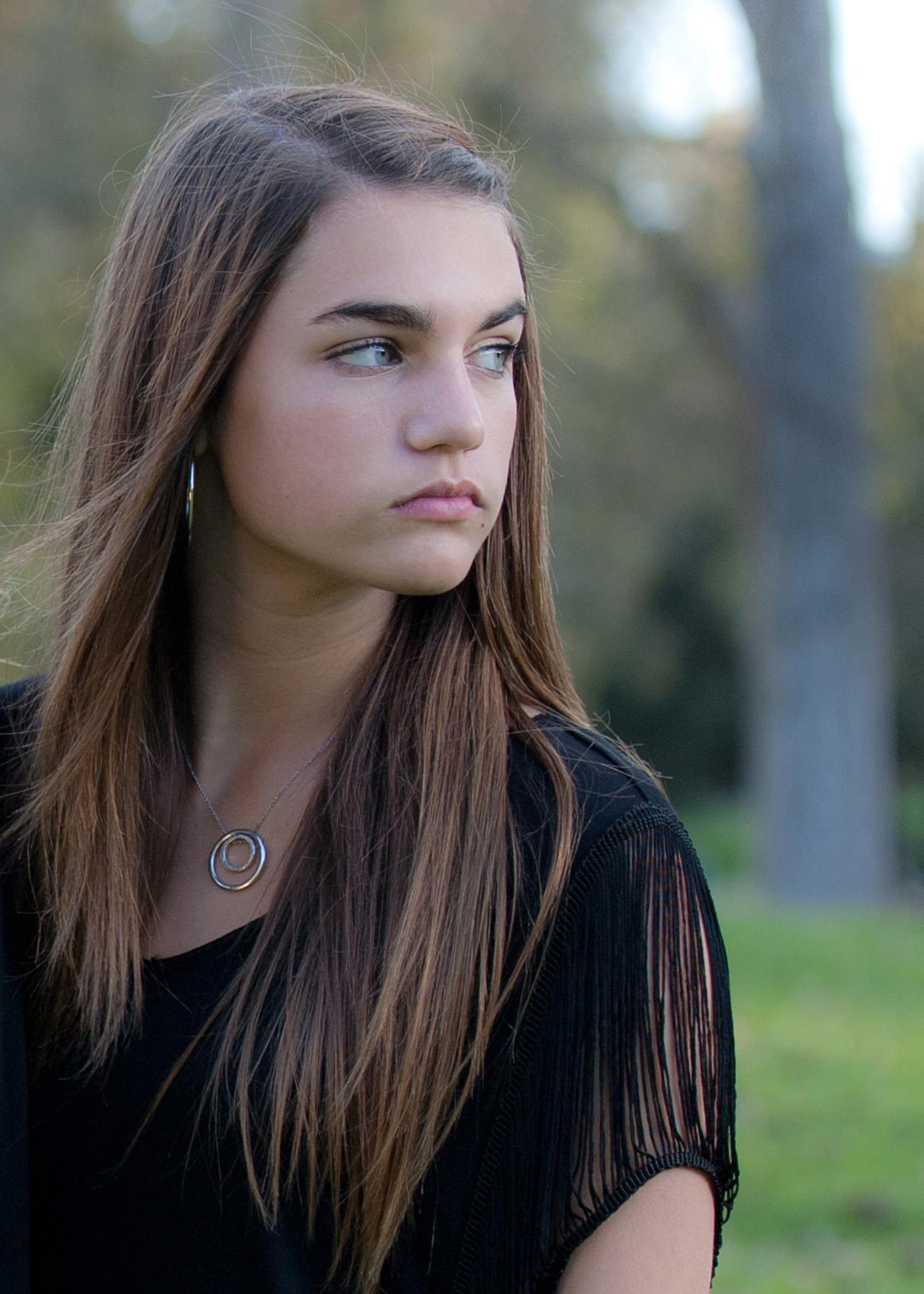teenage girl long brown hair park setting