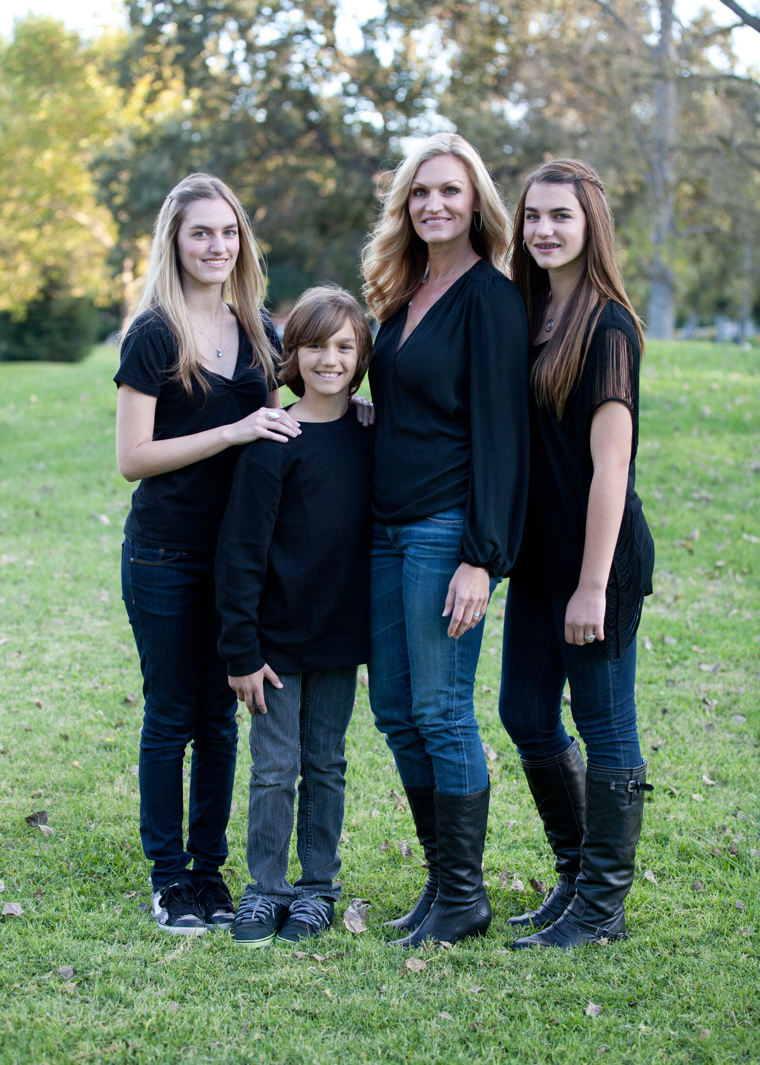 family portrait mother two daughters one son black shirts blue jeans park grass backdrop