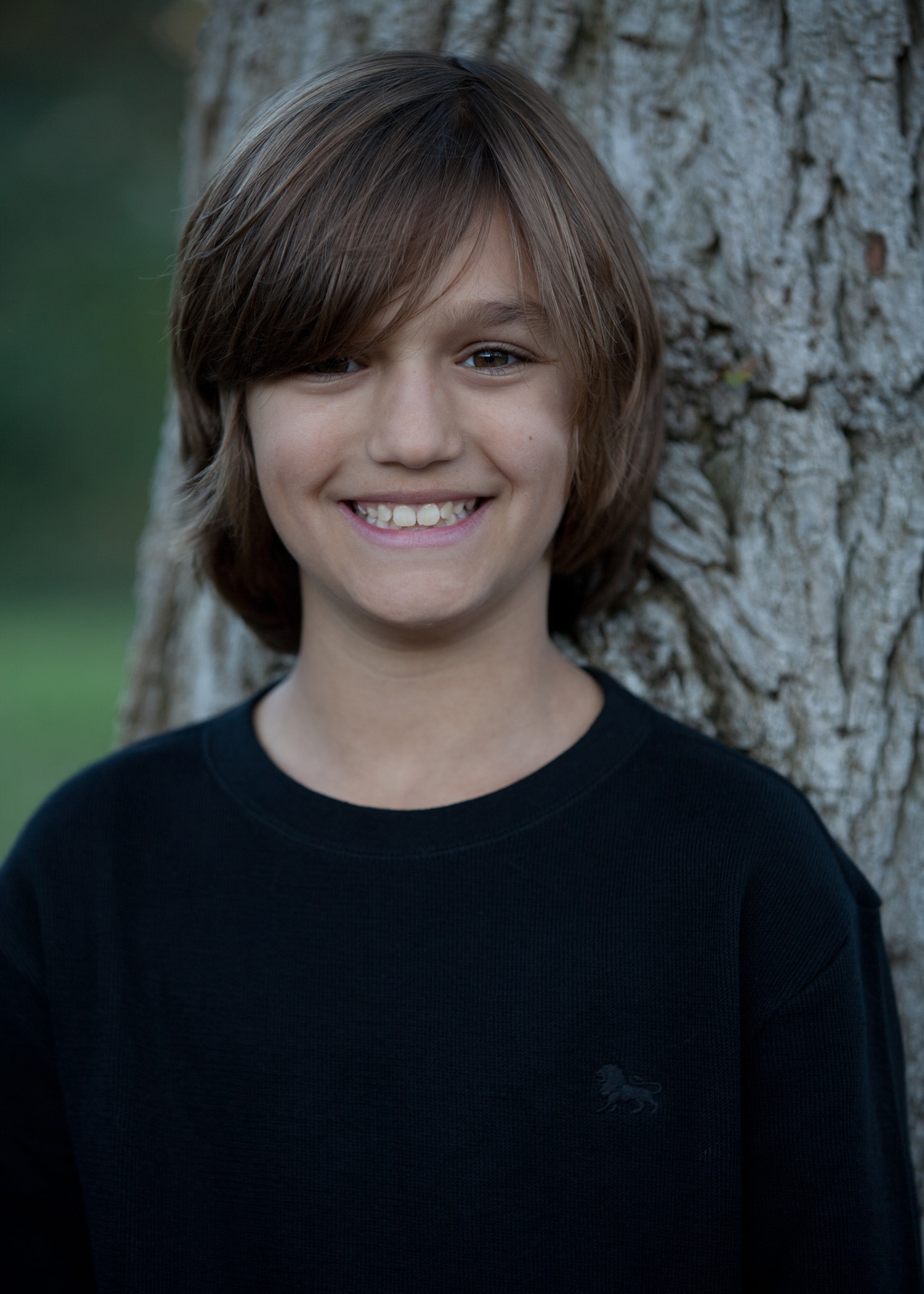 portrait young boy black shirt tree backdrop brown hair smiling