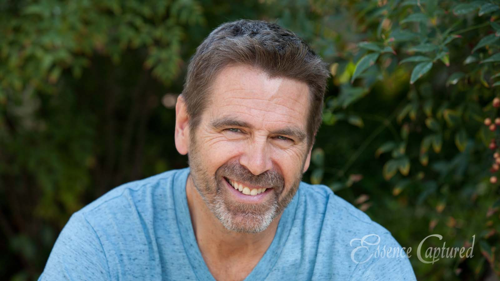 head shot older male facial hair natural background blue shirt