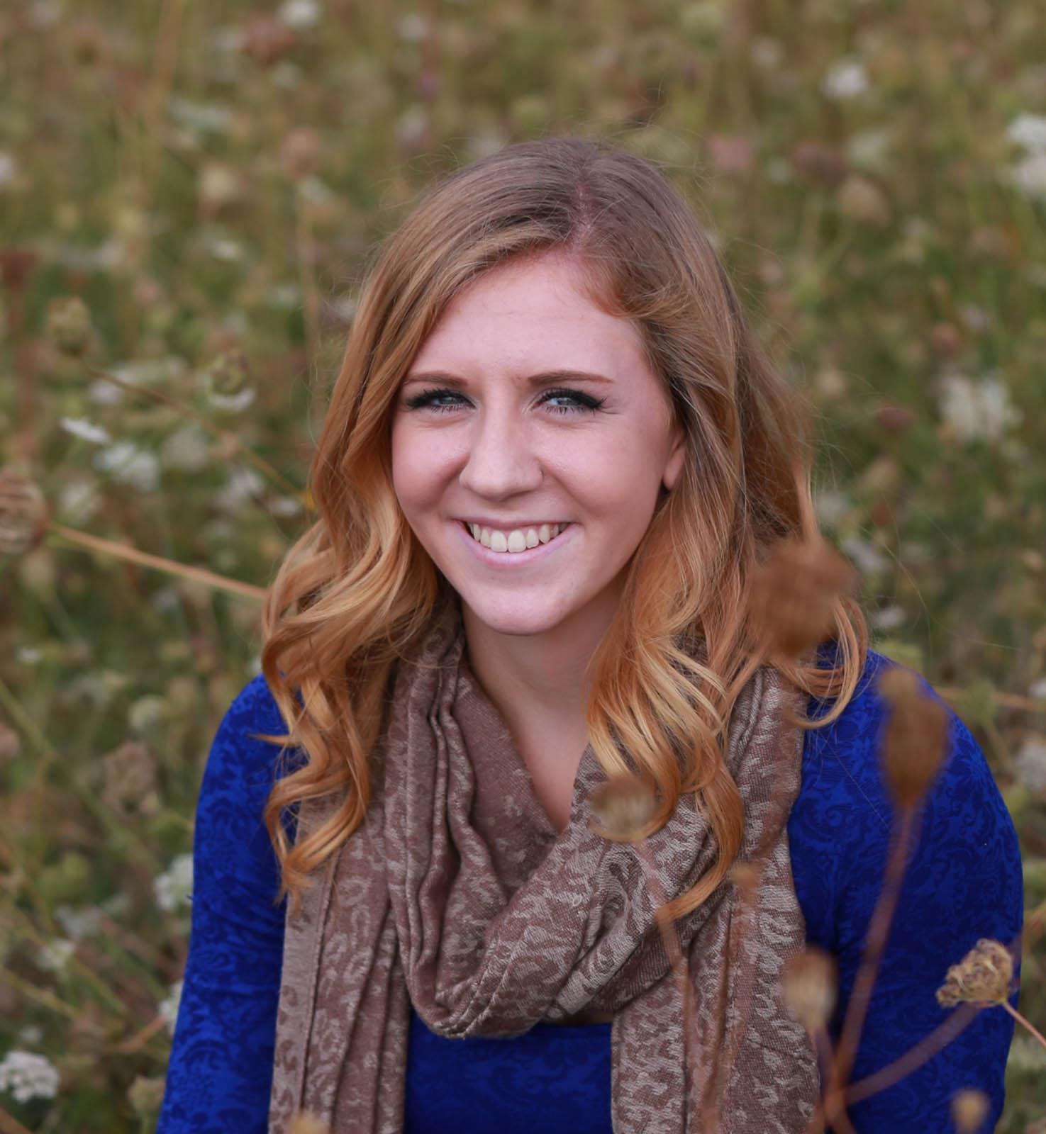 senior portrait female long blonde hair blue dress sitting in field