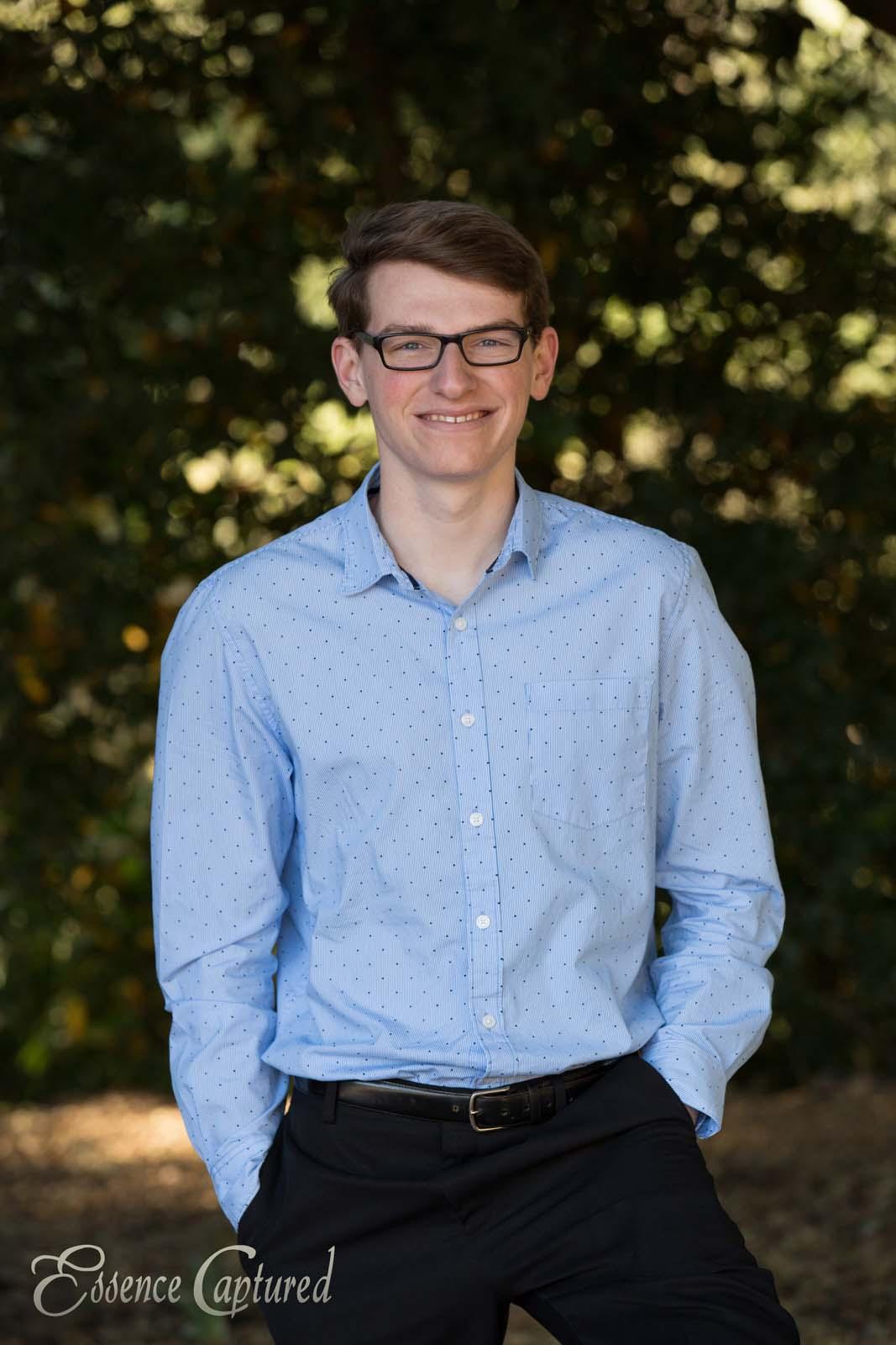 high school senior portrait male light blue long sleeve shirt dark green tree background glasses