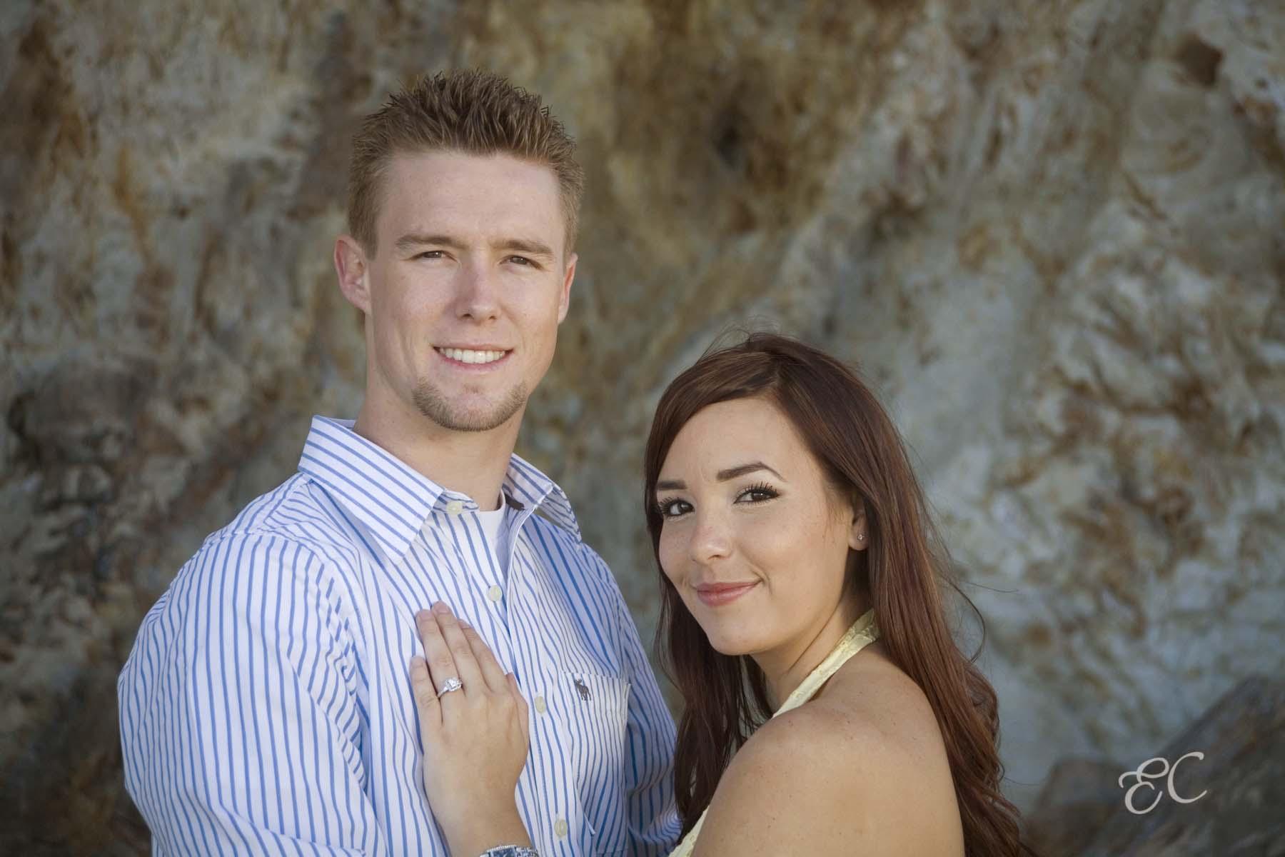 young couple celebrate engagement portrait rock backdrop