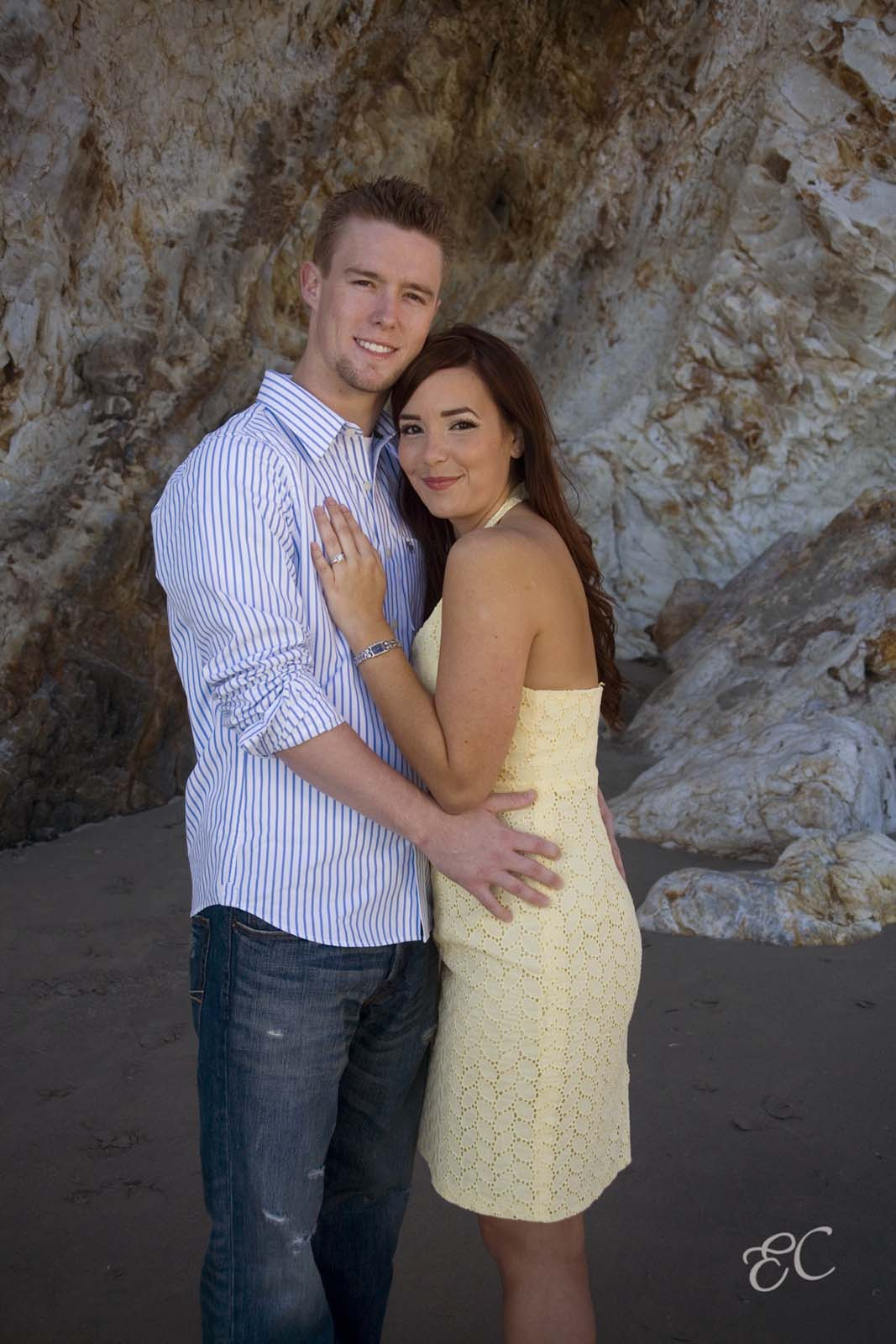 young couple celebrating engagement portrait at beach rock backdrop