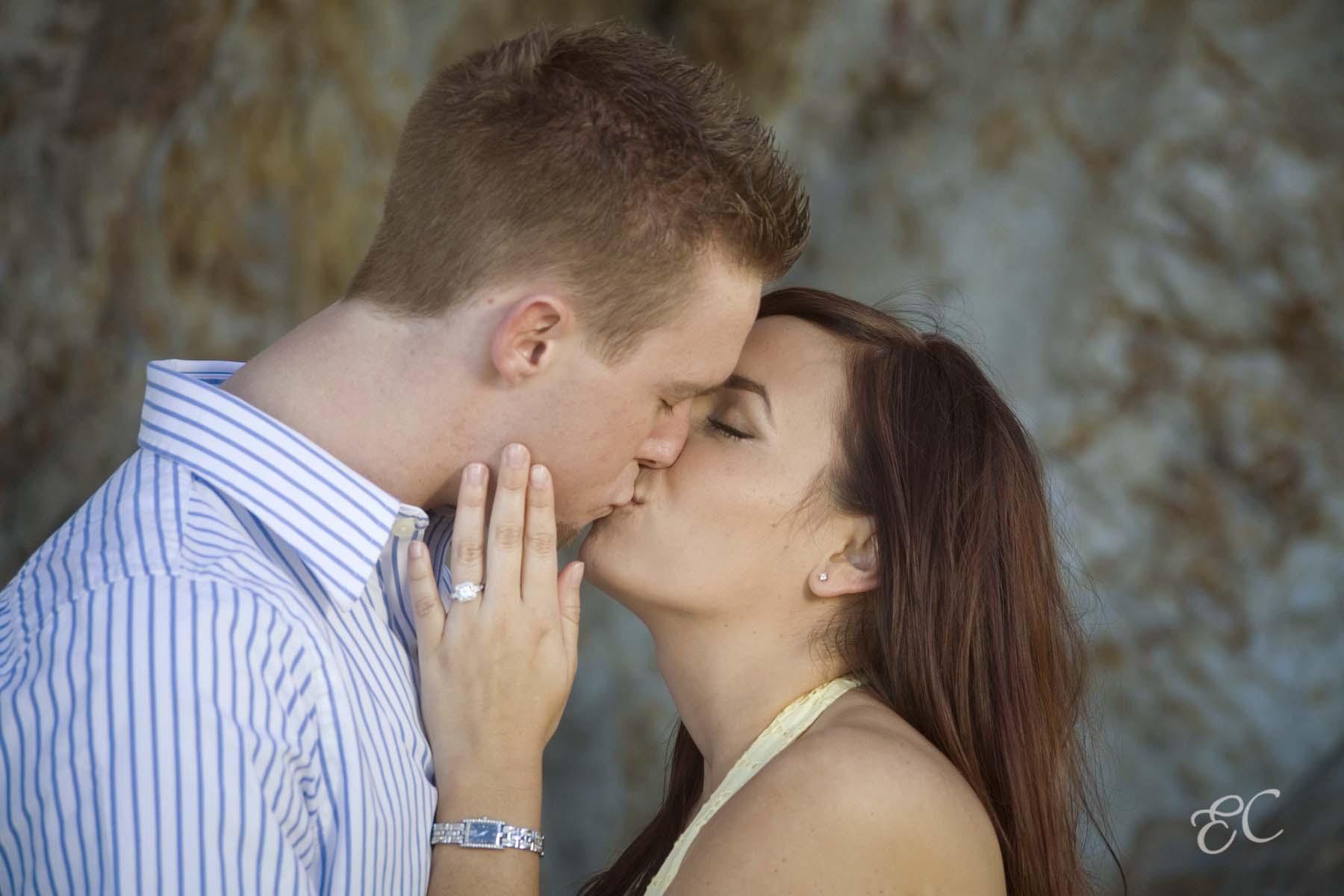 celebrating engagement kissing couple showing engagement ring
