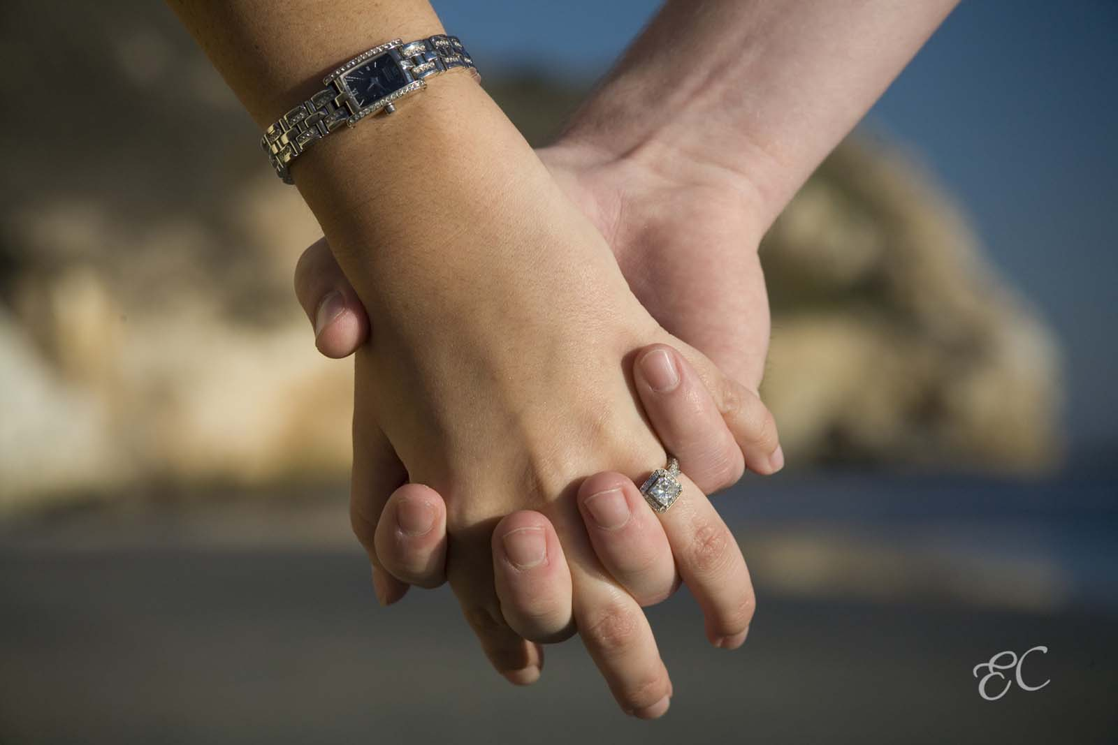 holding hands showing engagement ring walking on beach