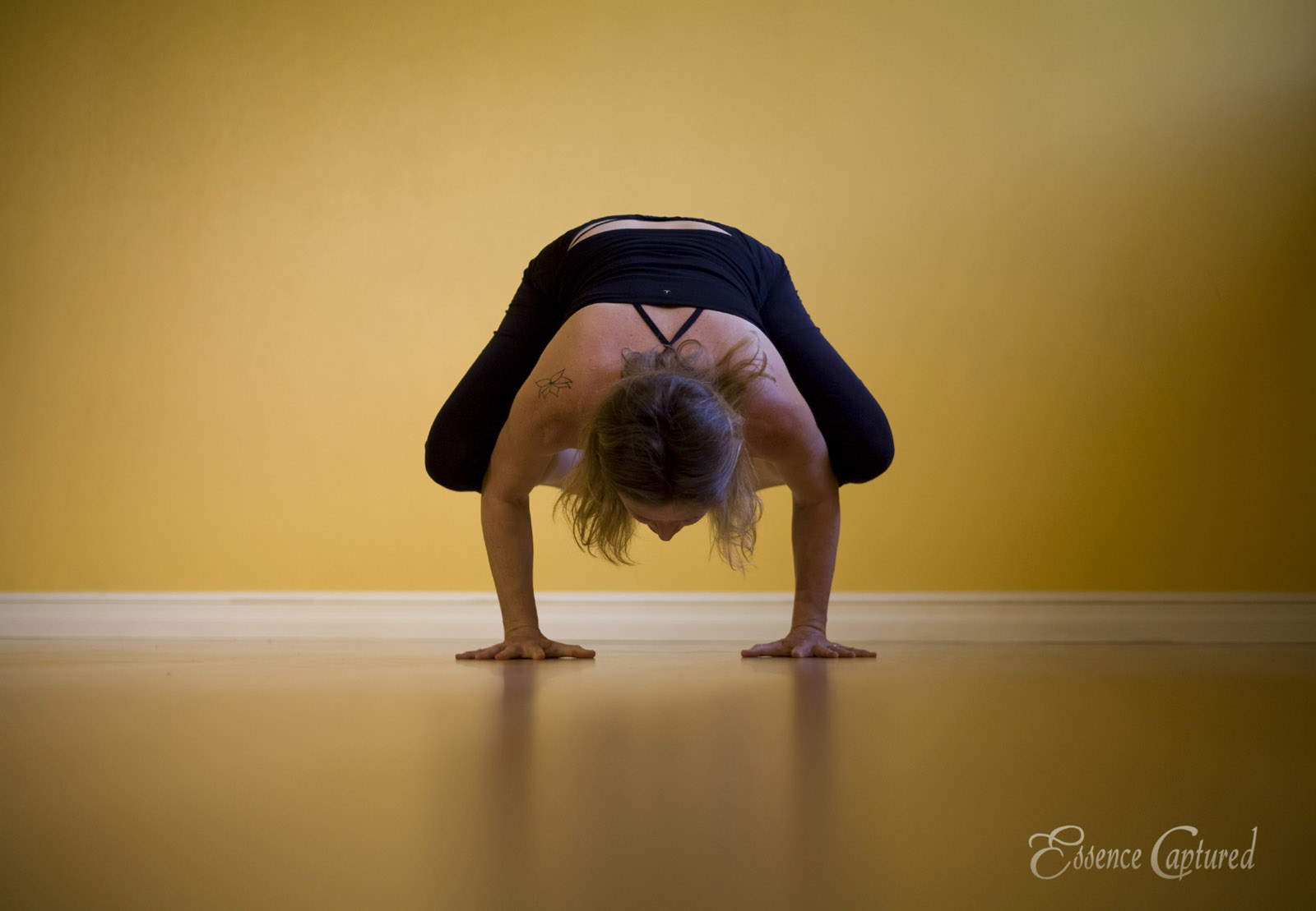 female yoga pose on hands yellow studio wall backdrop