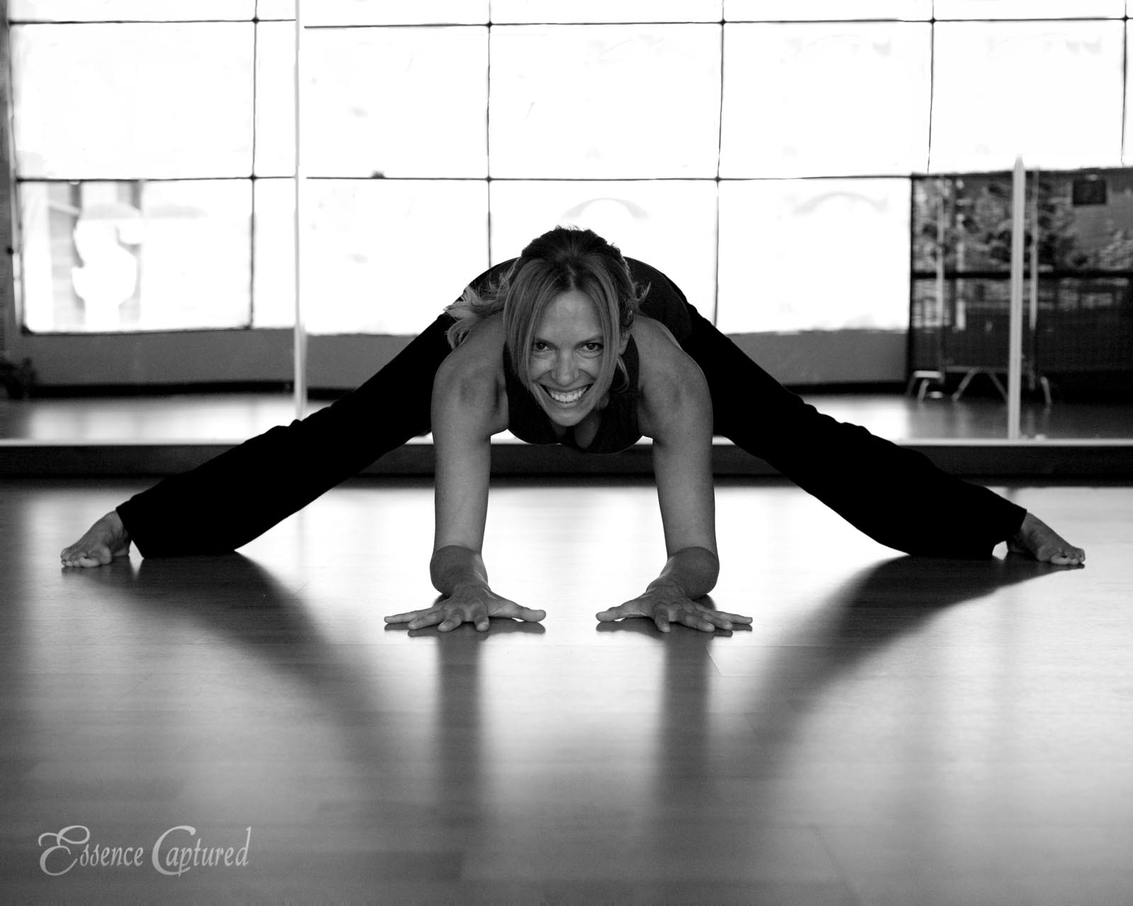female yoga instructor legs wide elbows on floor mirror backdrop reflecting window light