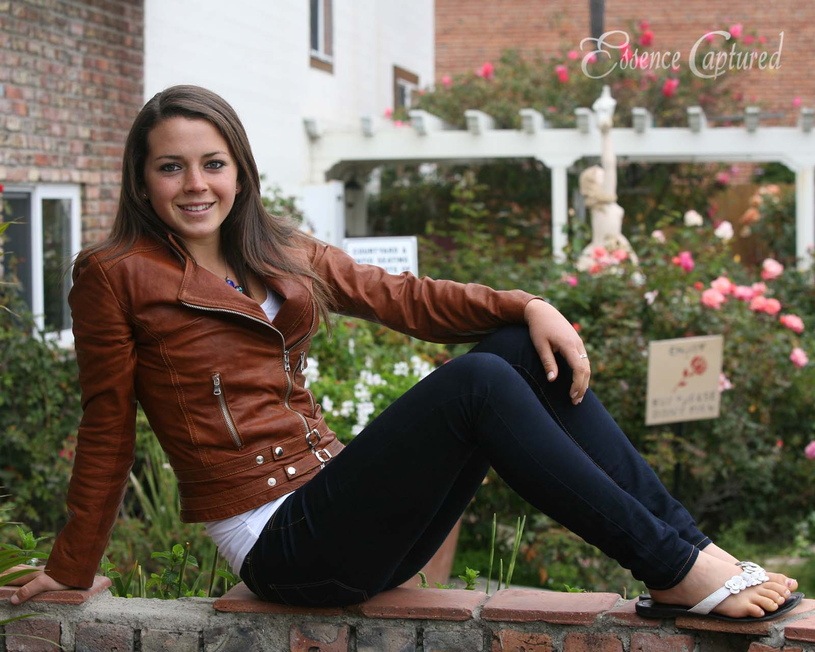 female high school senior portrait sitting on brick wall garden backdrop brown leather jacket long brown hair blue jeans casual