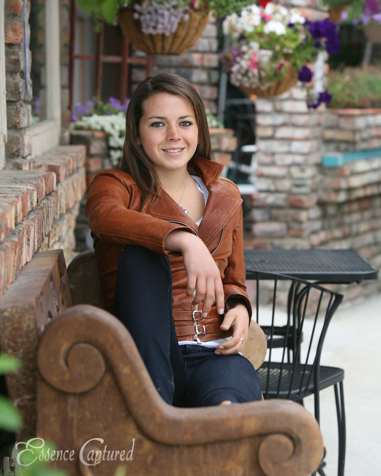 female high school senior portrait sitting on bench in outdoor cafe
