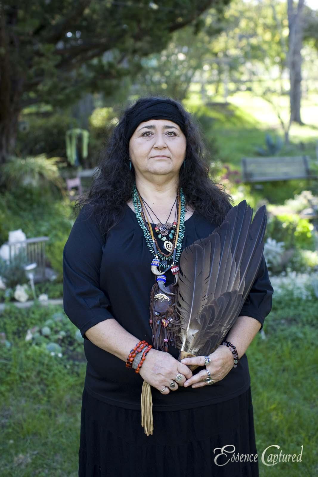 Native American Elder female clan mother portrait long black hair eagle feathers in garden