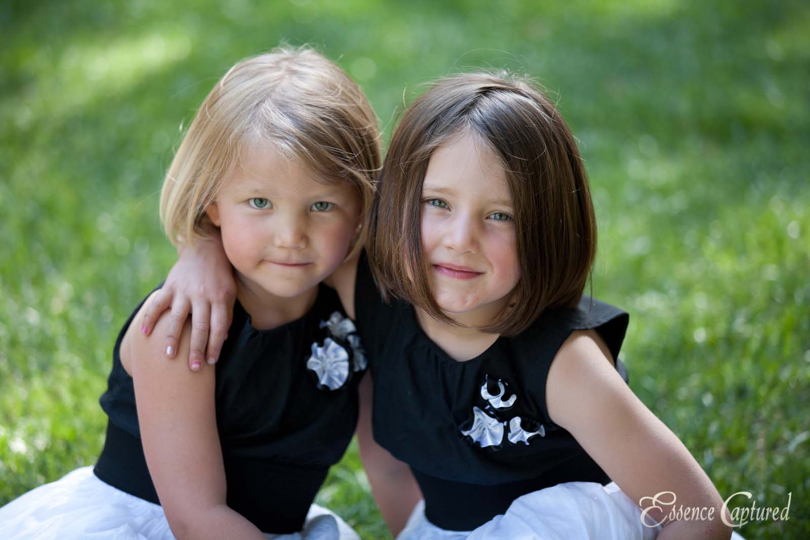 two sisters young arm in arm on grass