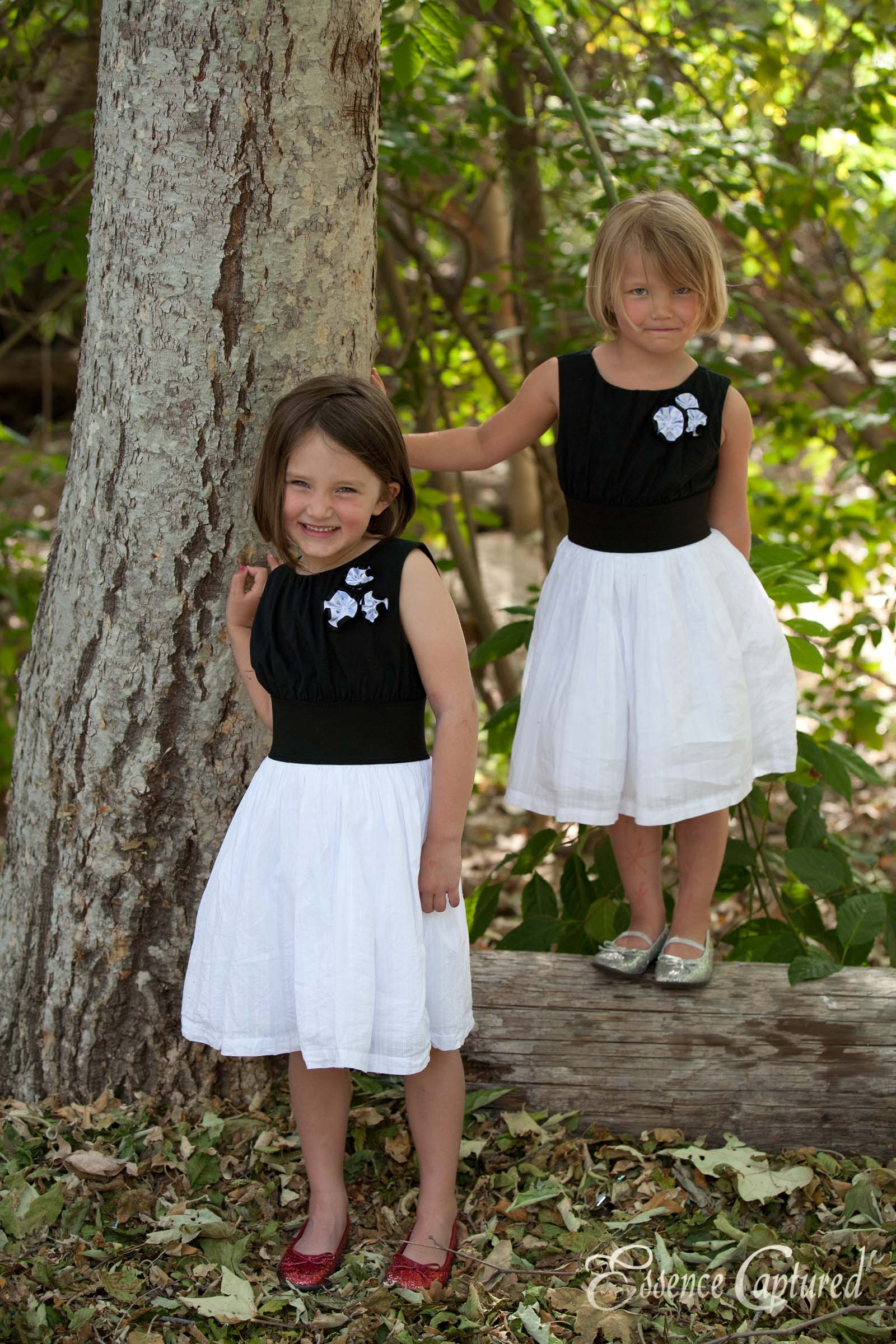 two young sisters matching dresses in park trees