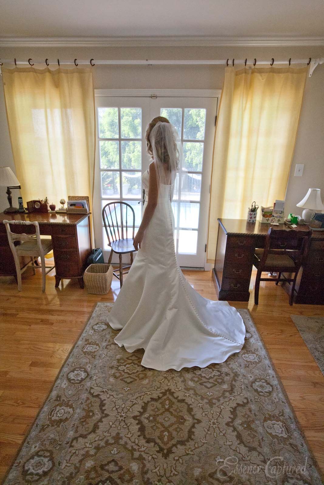 brides wedding dress in ready room looking out french doors