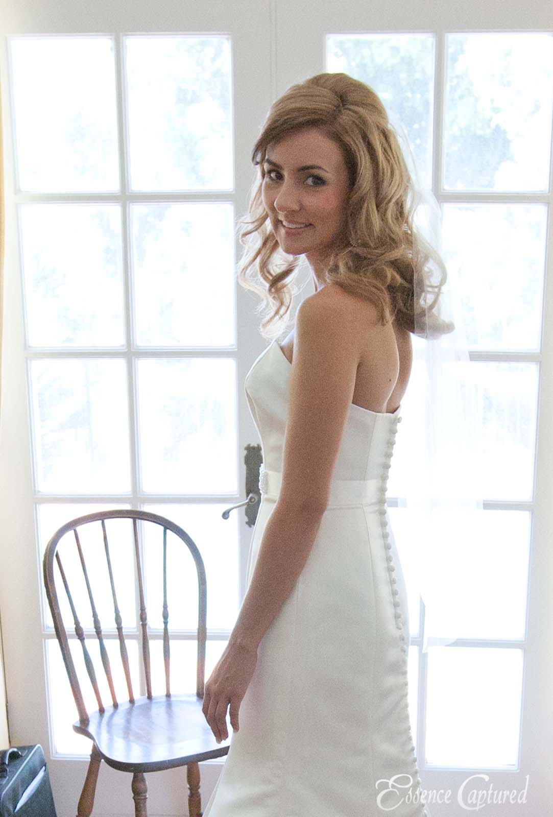 bride looks over her shoulder in ready room french doors as backdrop