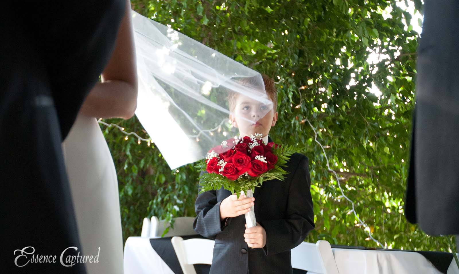 boy holds bouquet at wedding brides veil over his face faraway look