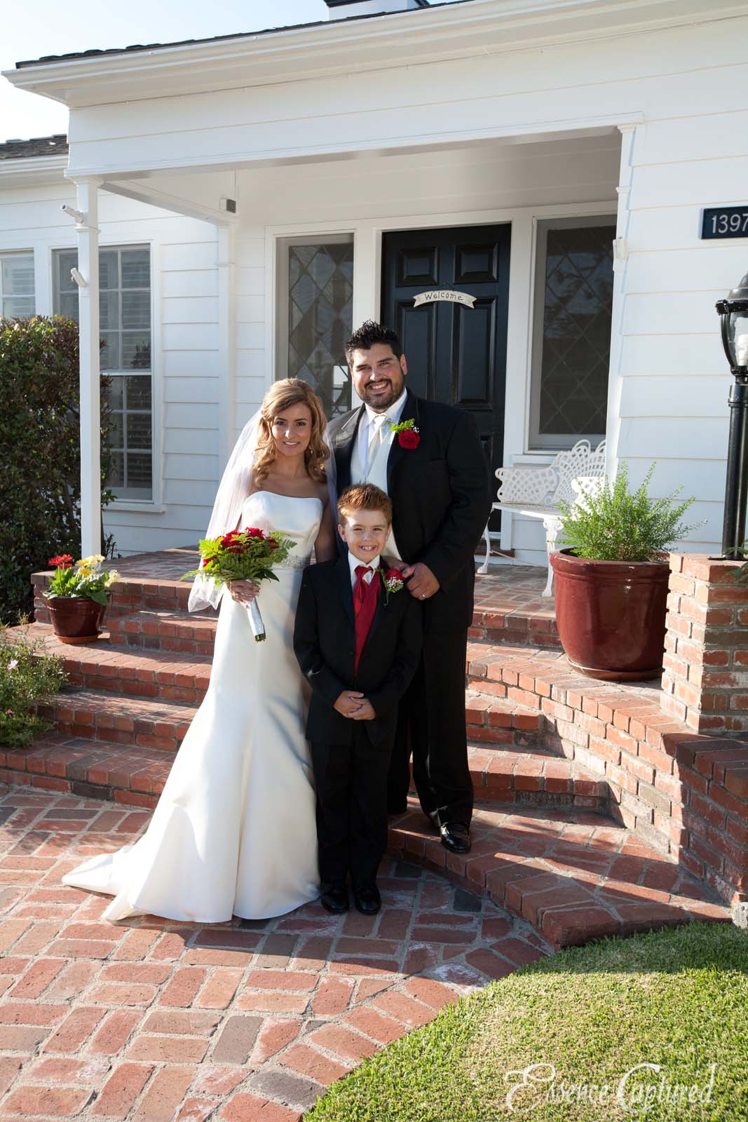 bride and groom and son in front of house after wedding