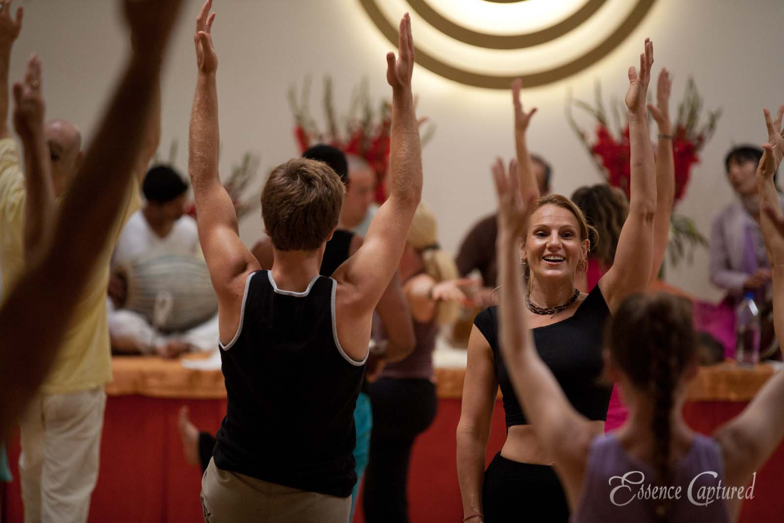 yoga instructor teaching class arms in air