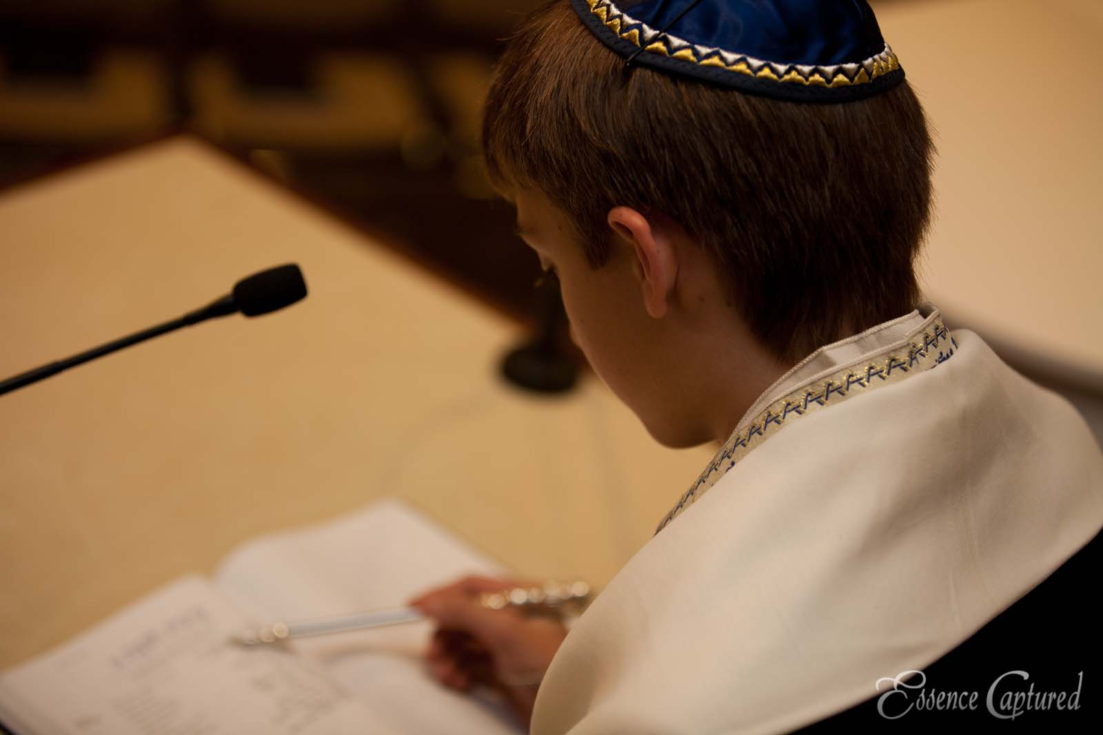 boy reading Hebrew at Bar Mitzvah looking over his shoulder