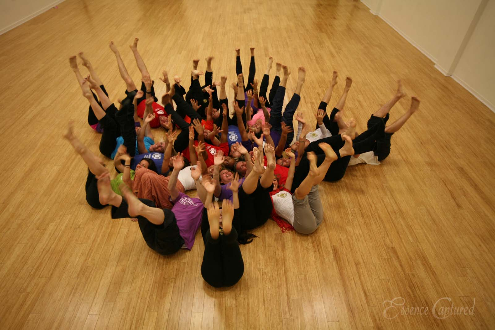 group of yoga teachers on backs in circle with hands and feet in the air