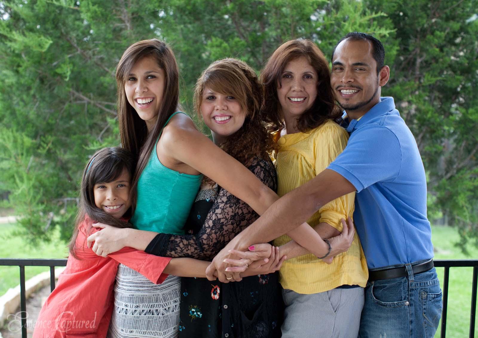 family of 5 hugging in back yard