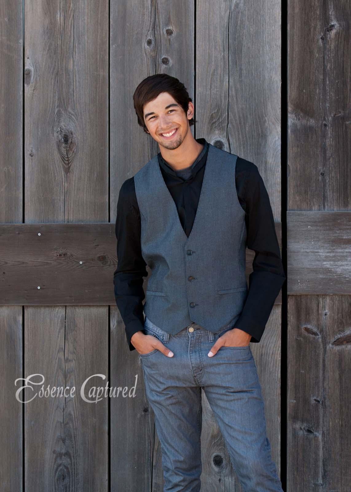 male high school senior portrait barn backdrop suit vest hands in pockets