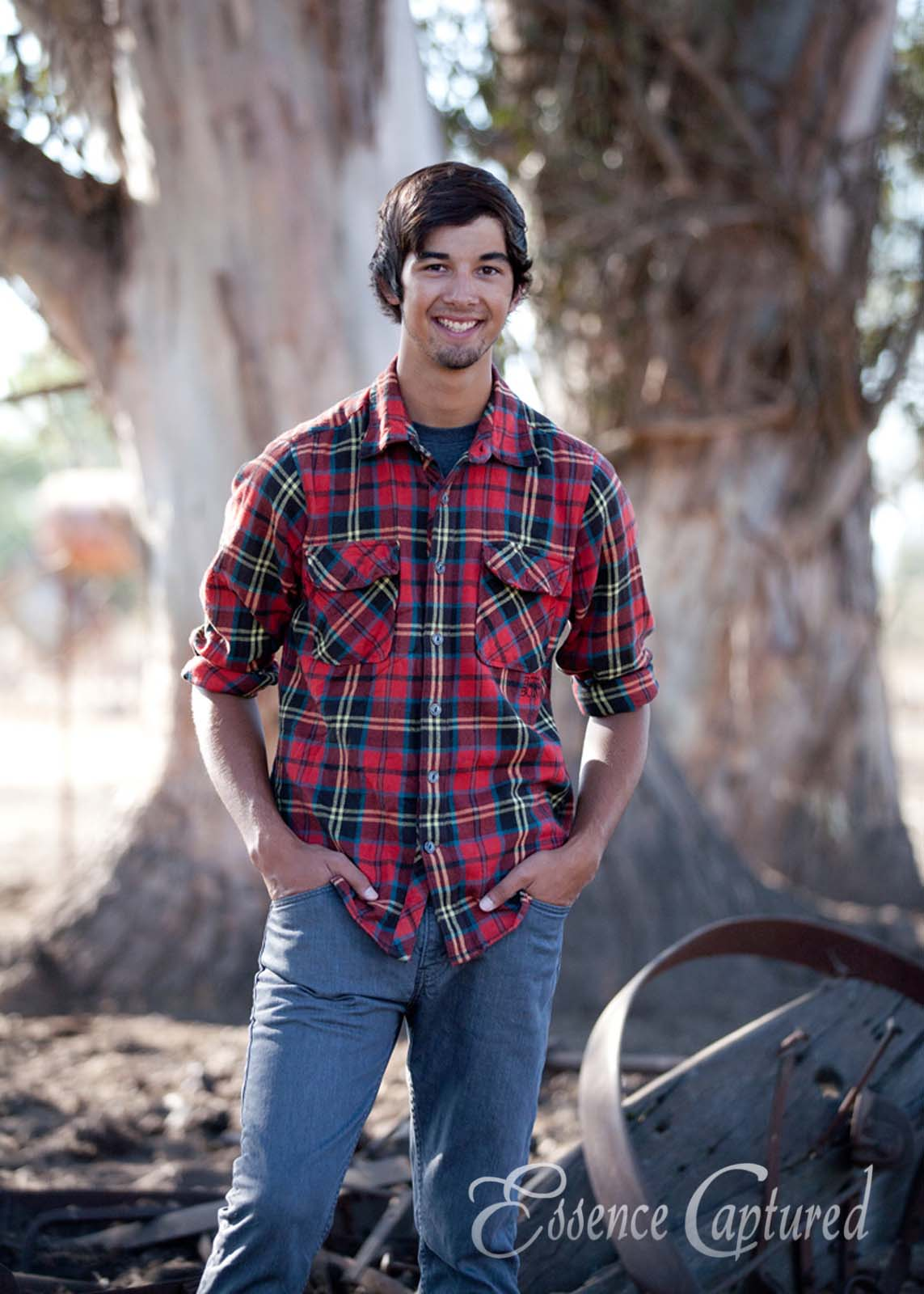 male high school senior portrait country theme red plaid shirt trees backdrop