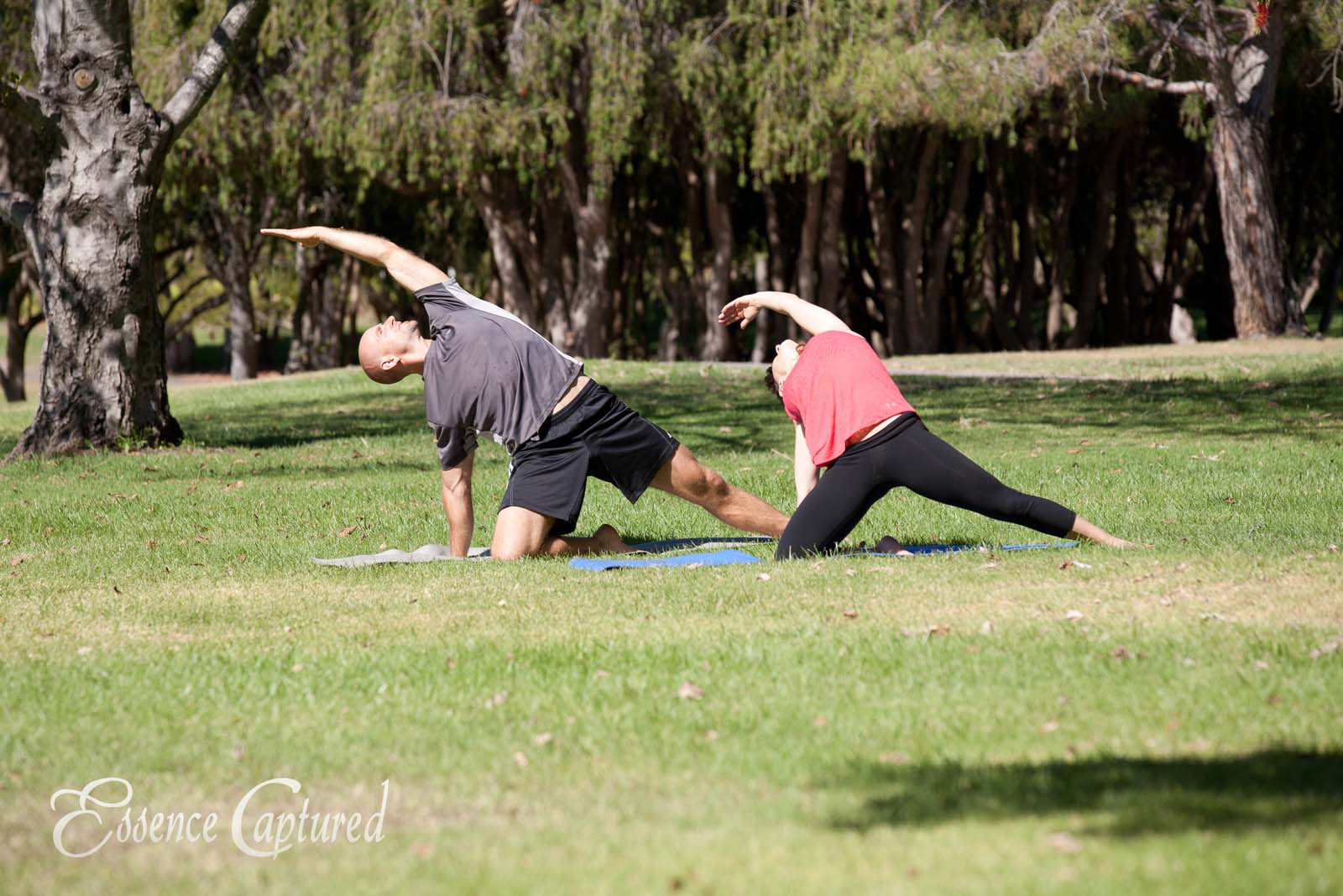man woman in park doing yoga stretch