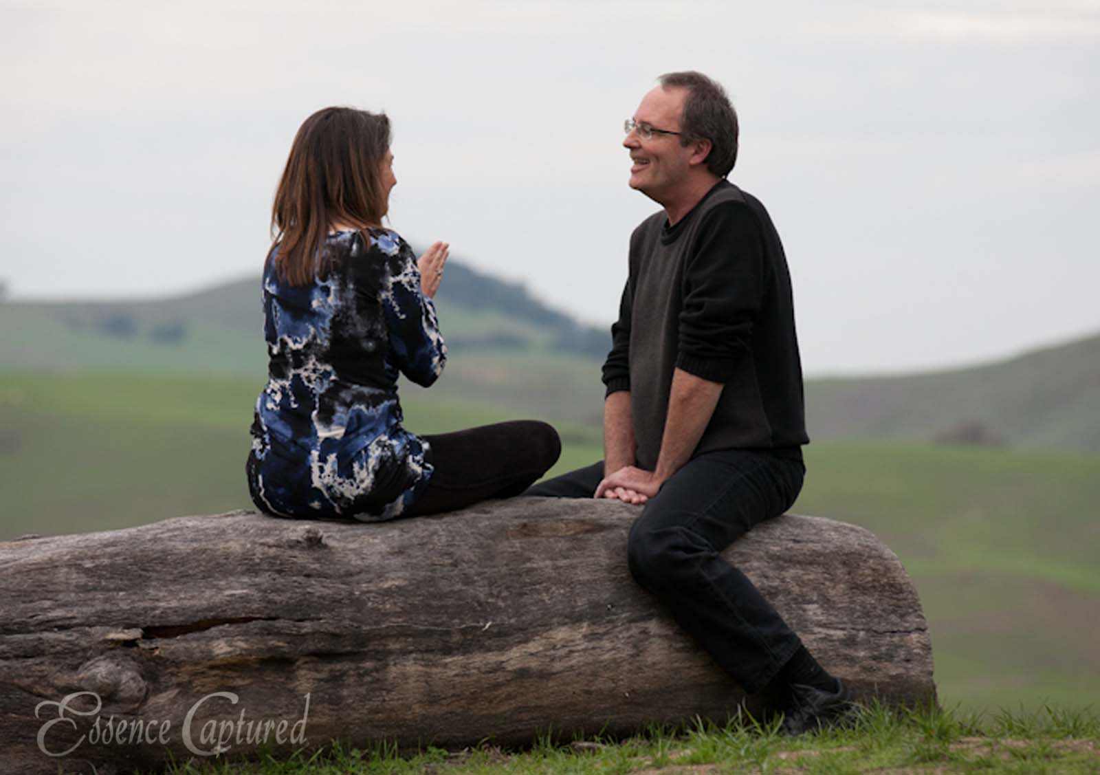woman and man talking sitting on tree log green hills in background