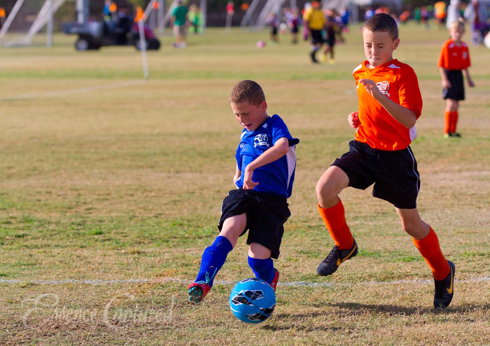 boy kicking soccer ball blue orange Conejo Valley