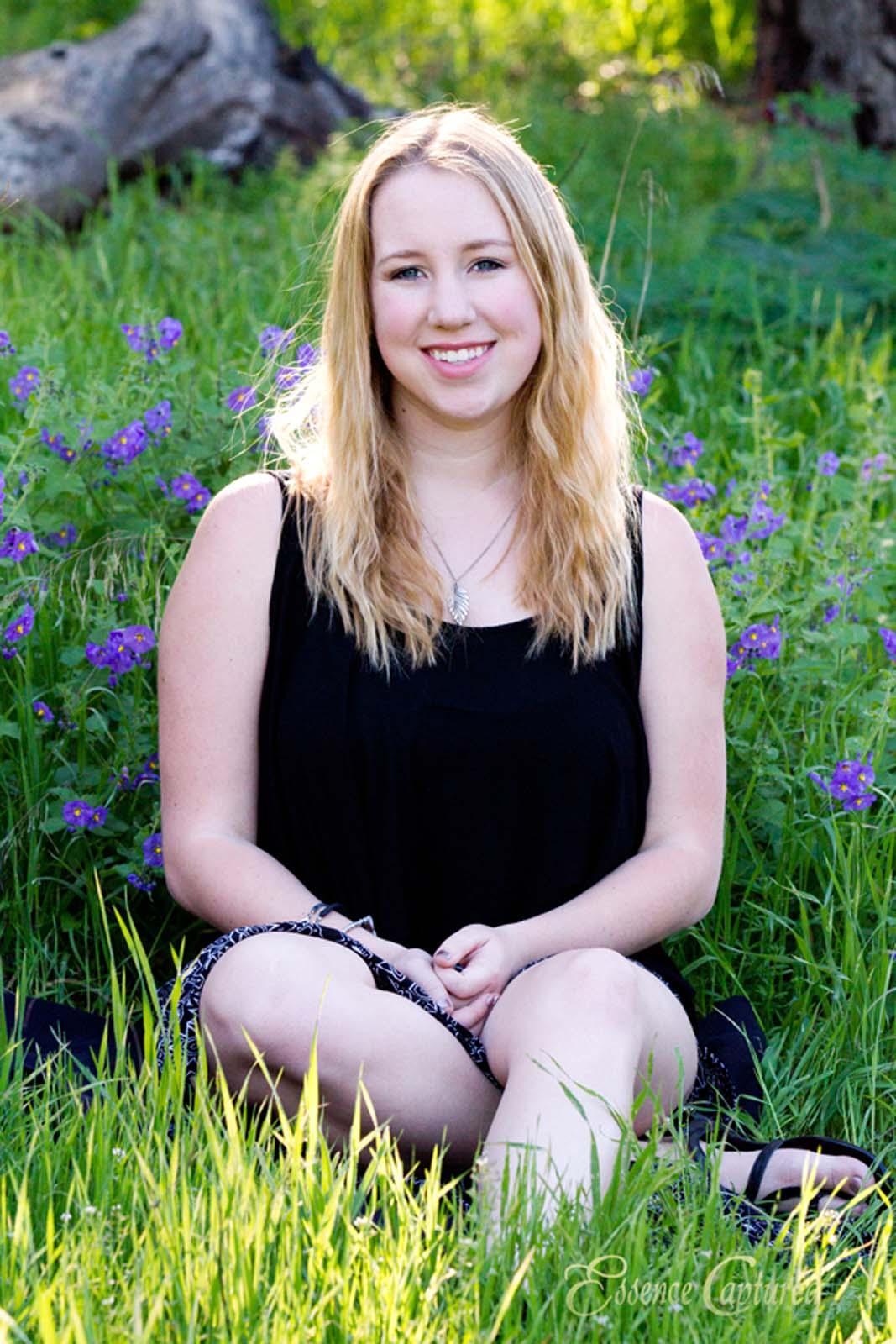female high school senior portrait blonde hair black dress sitting in spring setting purple wildflowers green grass
