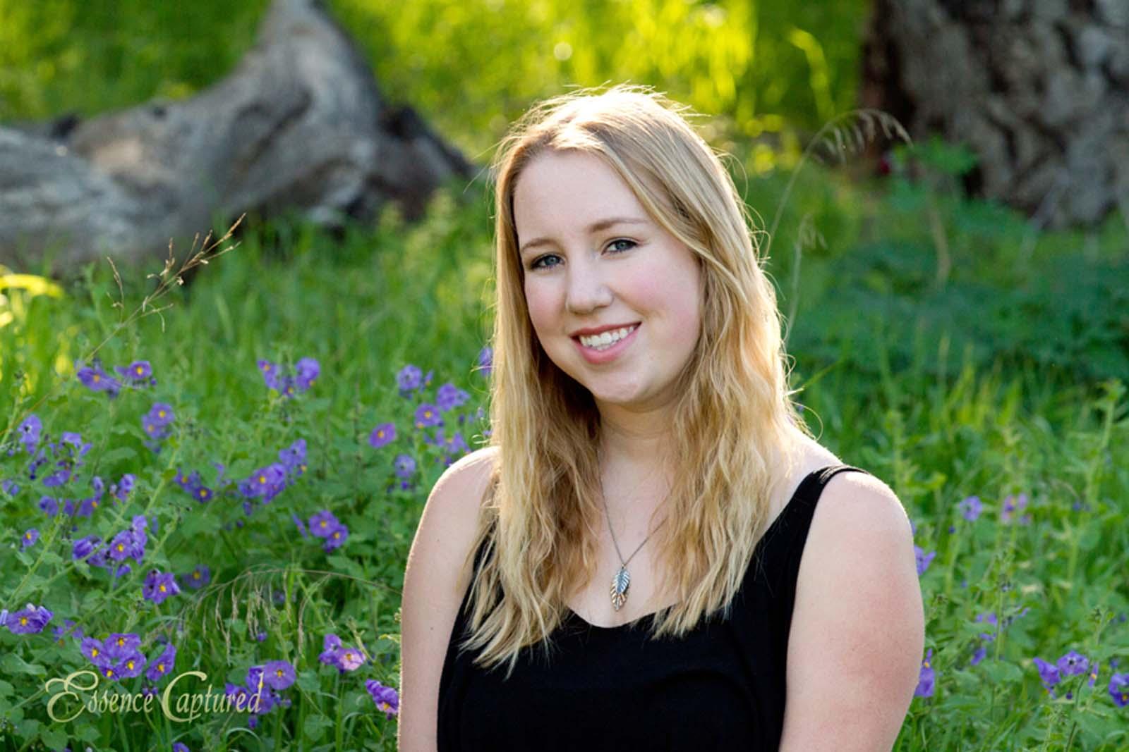 female high school senior portrait sun highlighting blonde hair green grass purple wildflowers
