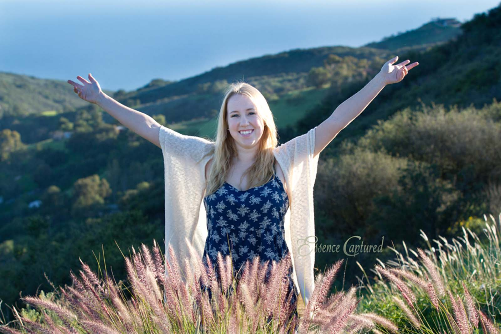 female high school senior portrait celebration top of mountain hills and ocean in background