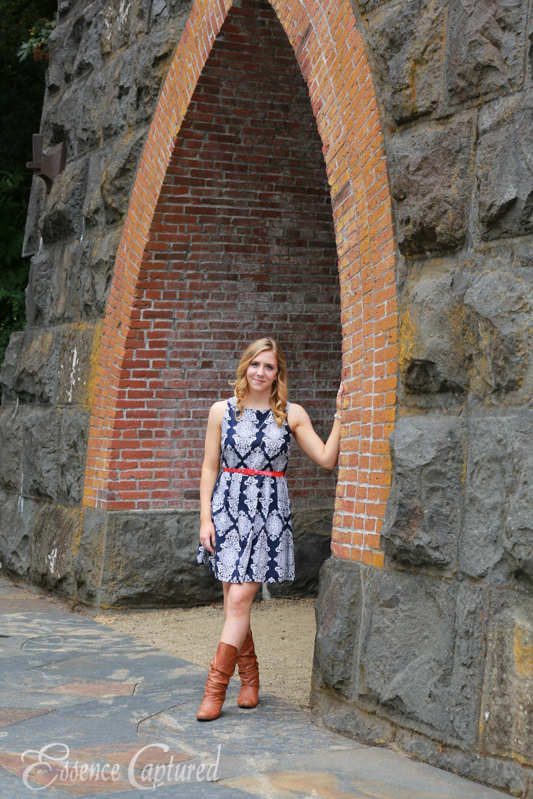 female high school senior portrait blue print dress long blonde hair standing in archway stone building