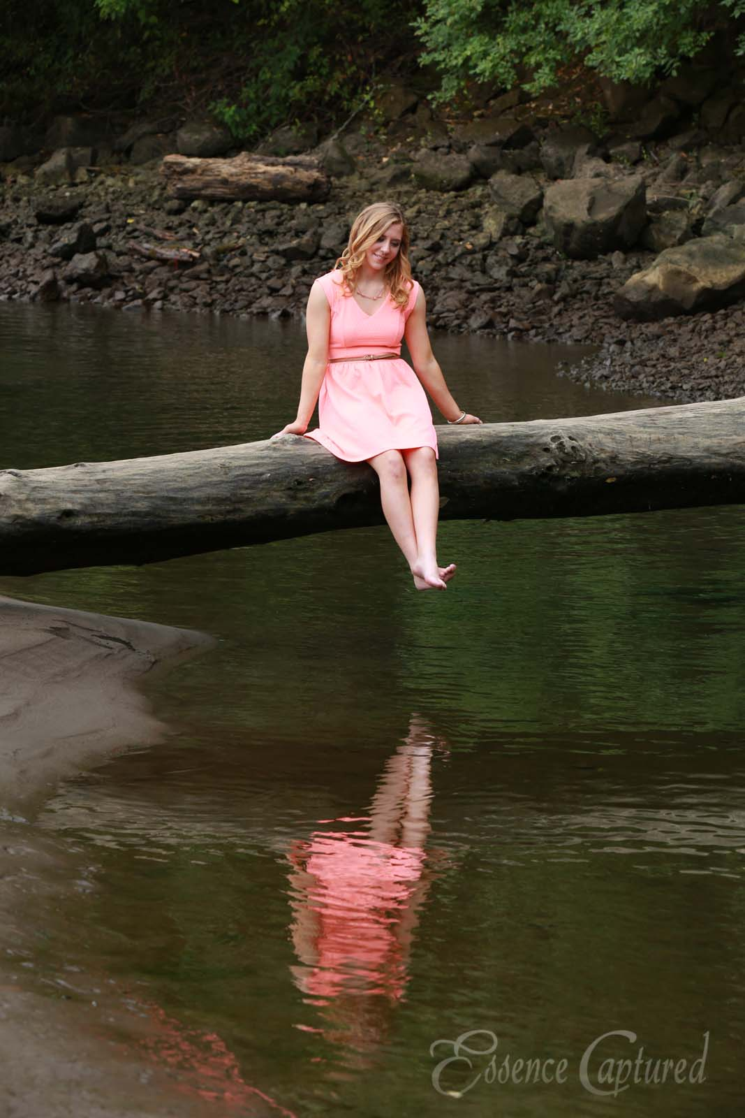 female high school senior portrait peach dress long blonde hair sitting on log above river reflection in water