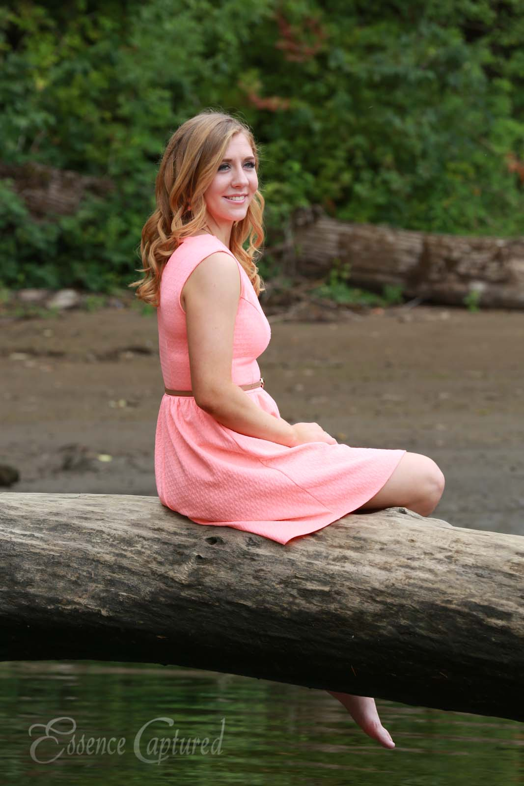 female high school senior portrait peach dress long blonde hair sitting on log above river looking over right shoulder