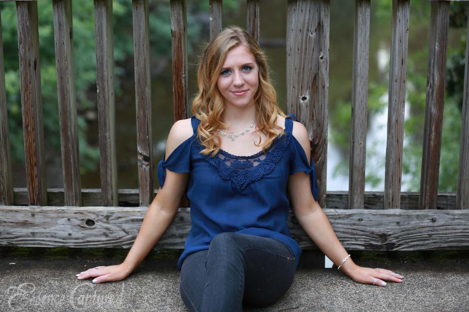 female high school senior portrait blue top long blonde hair sitting on bridge over river