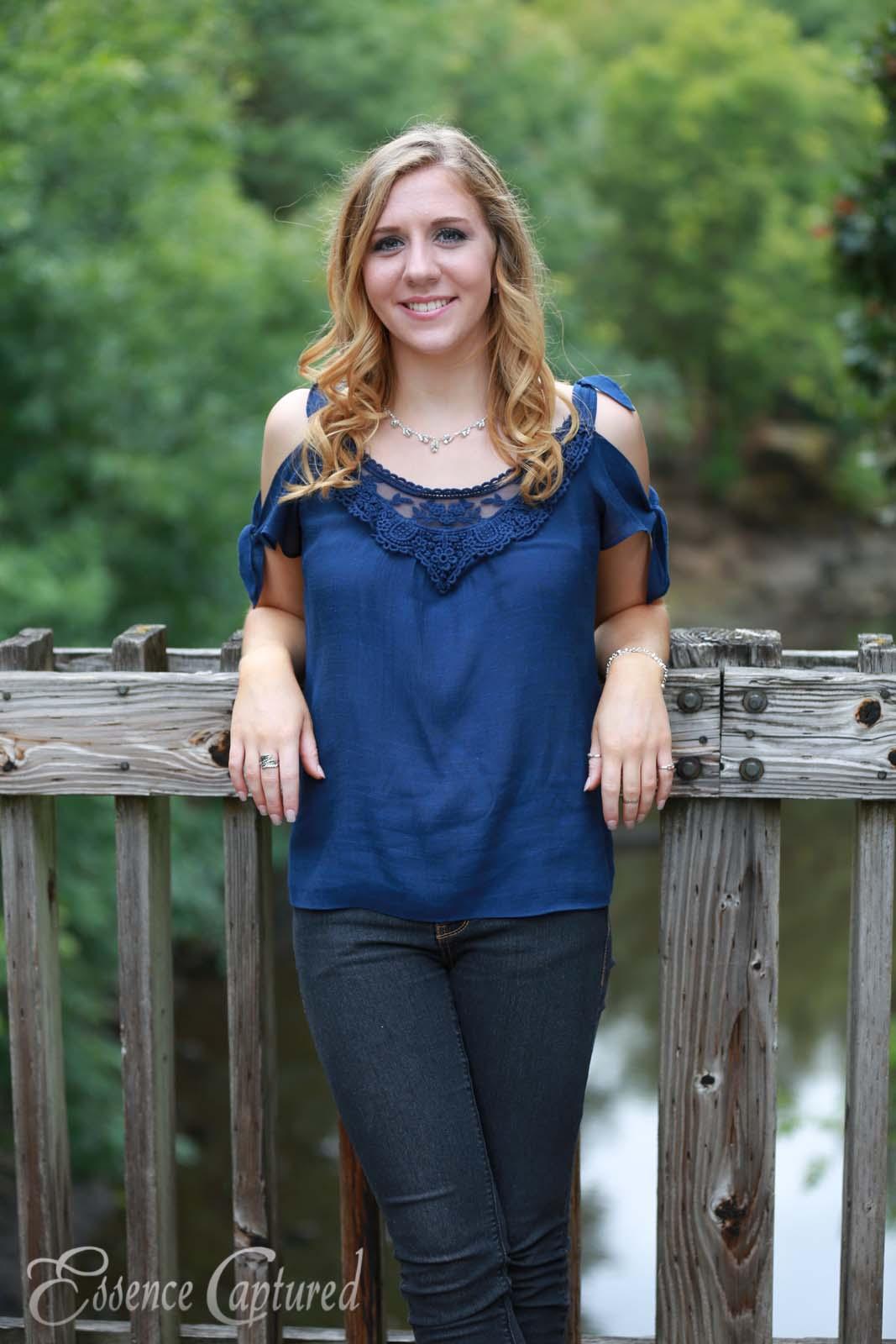 female high school senior portrait blue top long blonde hair standing on bridge over river