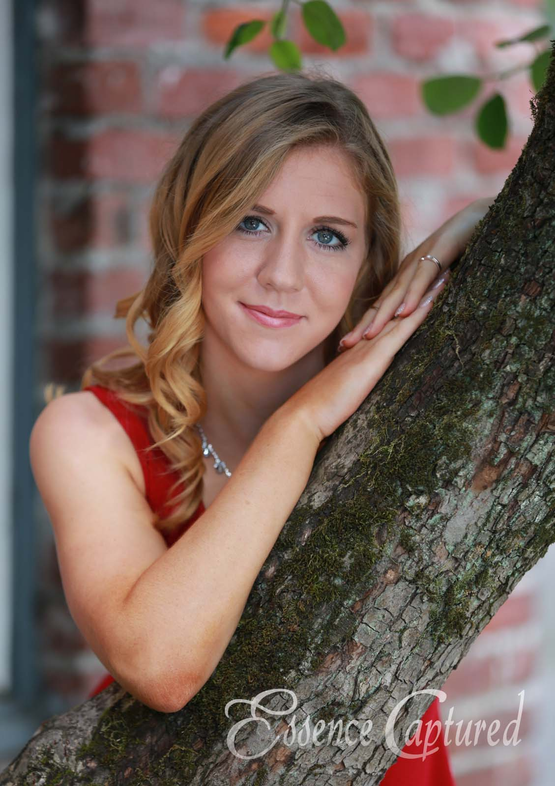 female high school senior portrait red dress long blonde hair leaning on tree brick backdrop