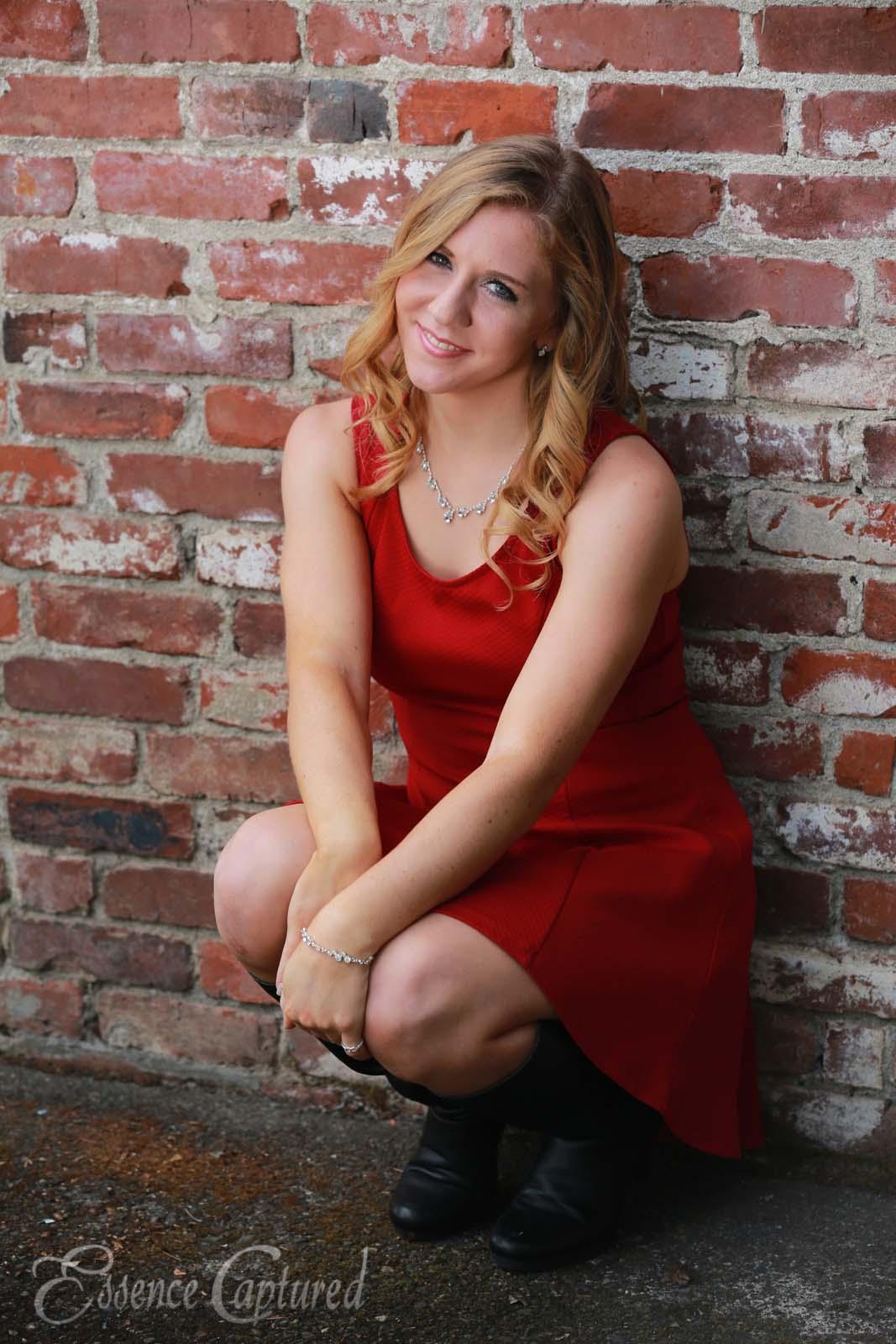 female high school senior portrait red dress long blonde hair brick backdrop