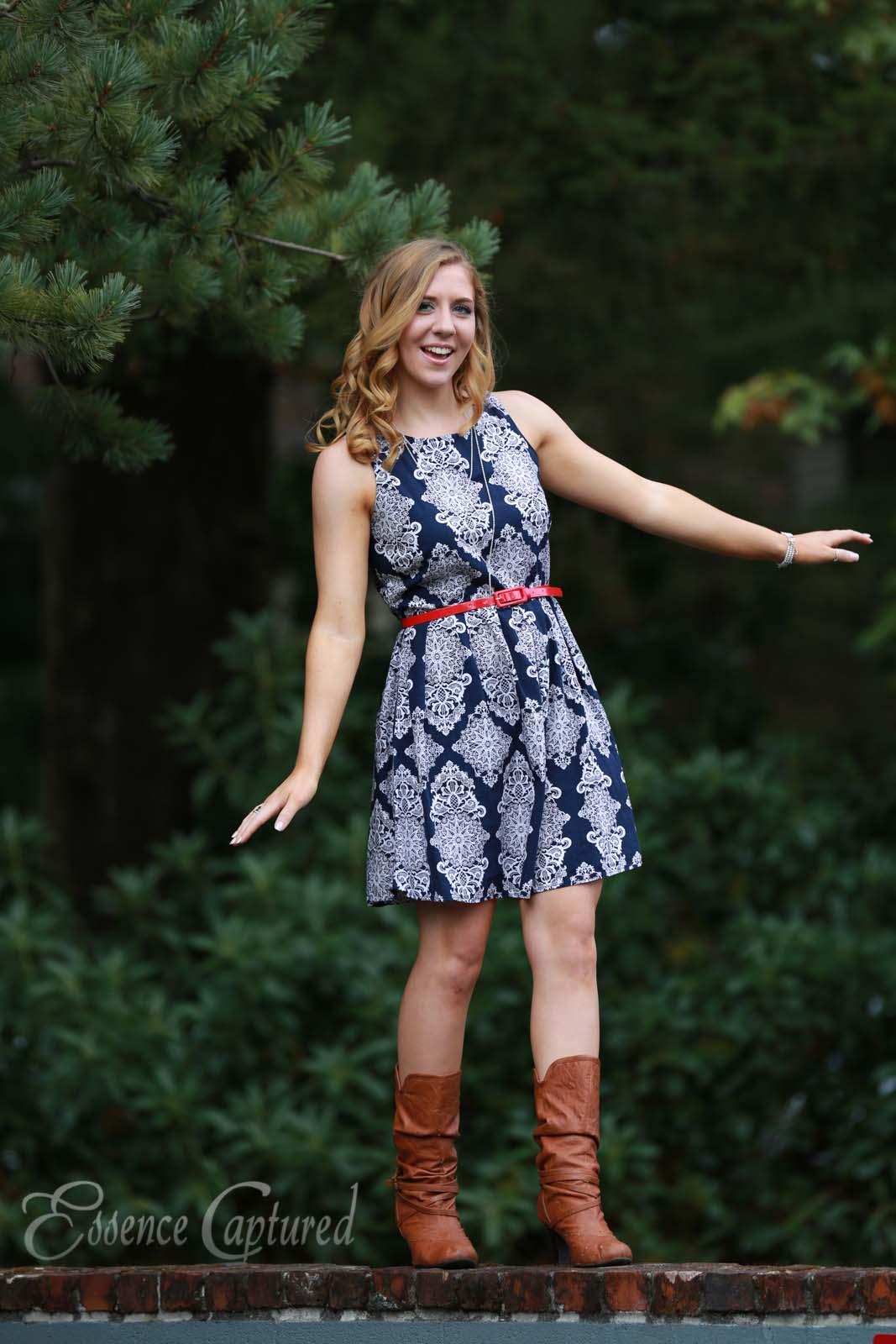 female high school senior portrait blue print dress long blonde hair walking on wall dark green natural background