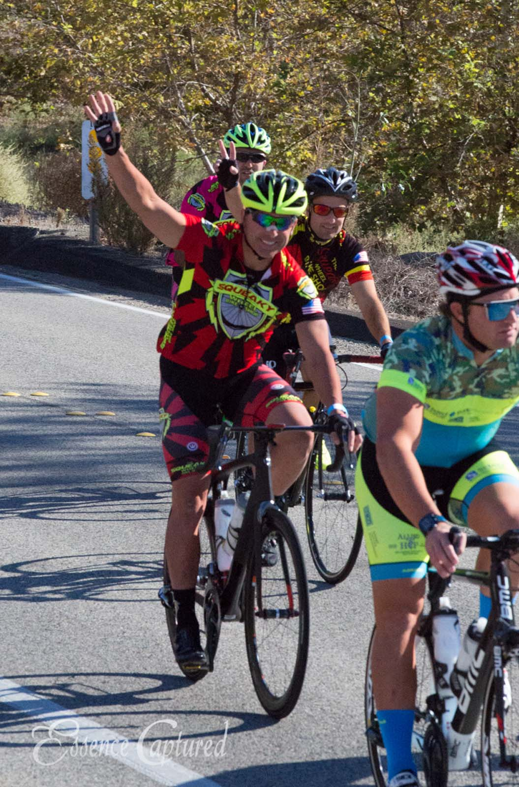 Mike Nosco Memorial Bike Ride cyclist waving red striped jersey green helmet