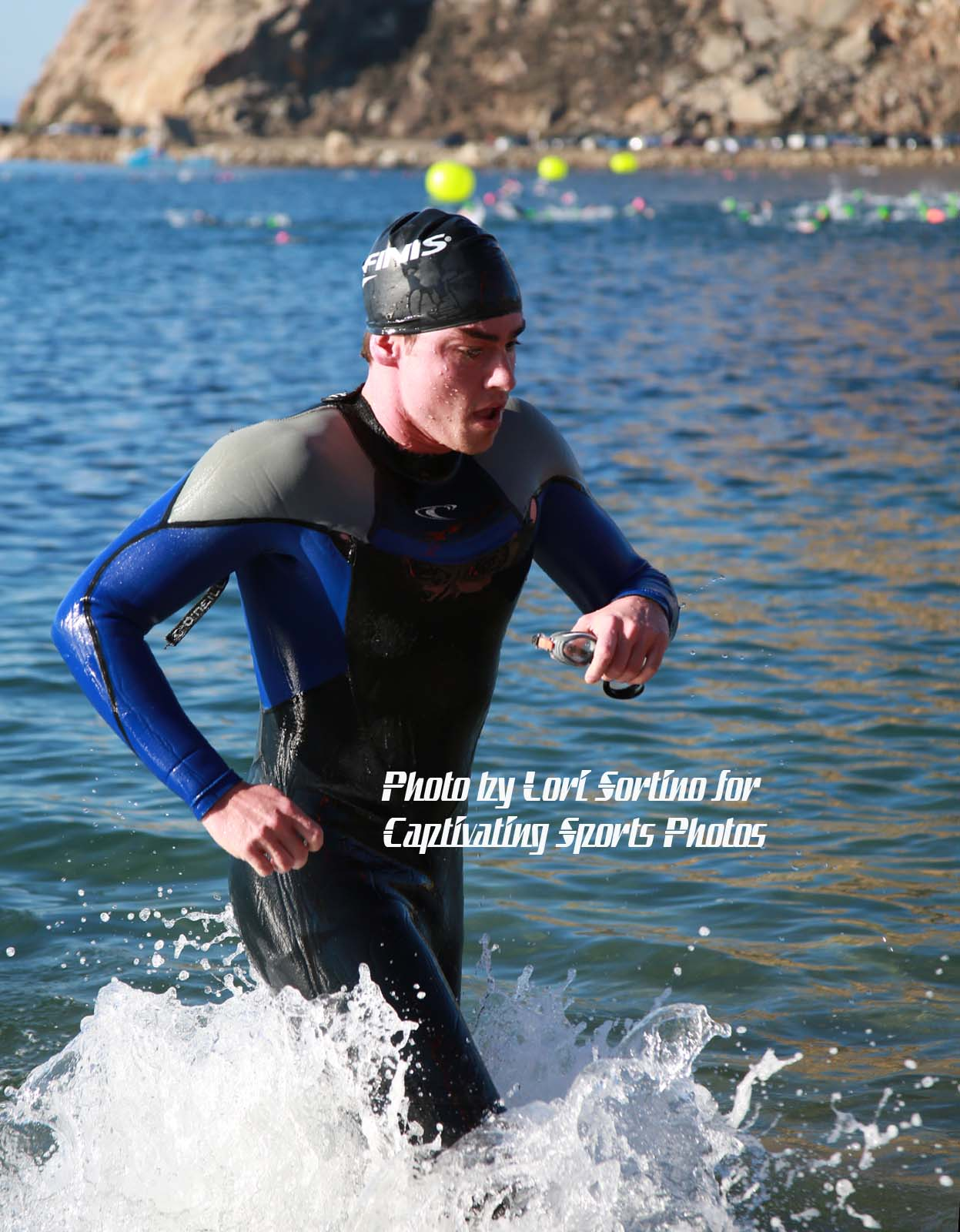 triathlete exiting water black swim cap
