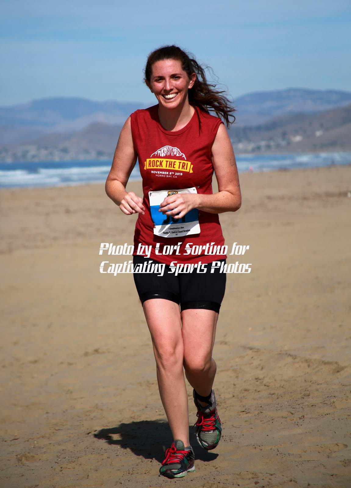 female triathlete running on beach red shirt long brown hair Morro Bay Tri