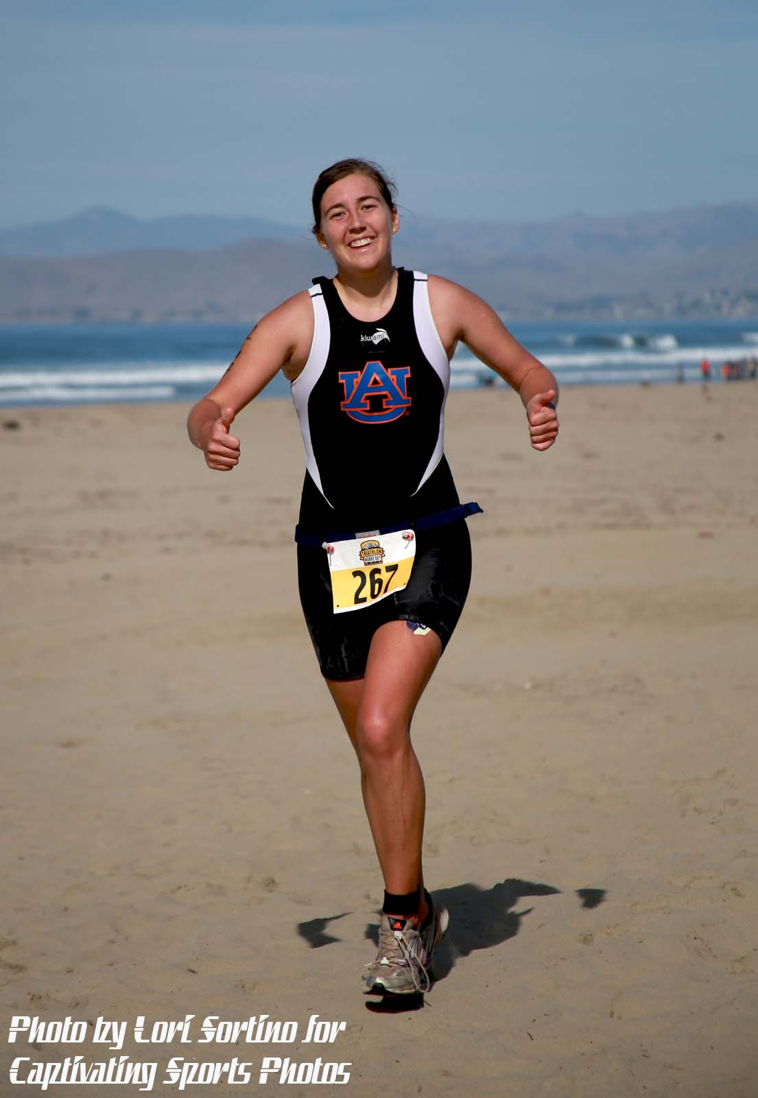female triathlete running on beach thumbs up smiling Morro Bay Tri