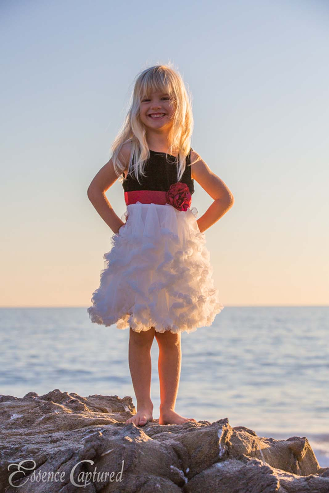young girl blonde hair fancy dress on rock at beach sunset ocean