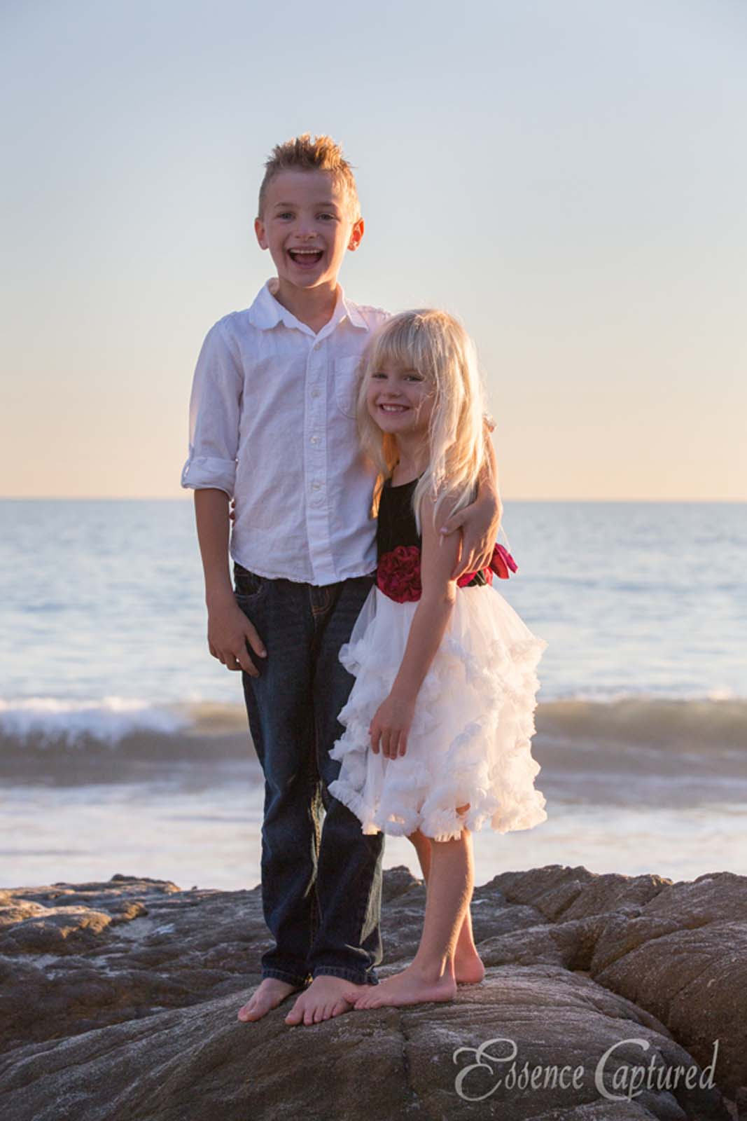 happy brother sister portrait at beach sunset ocean dressed up