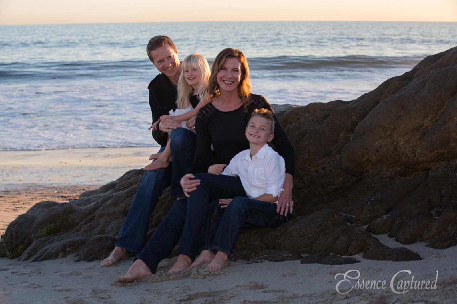 beach family portrait sunset sitting on rock ocean backdrop