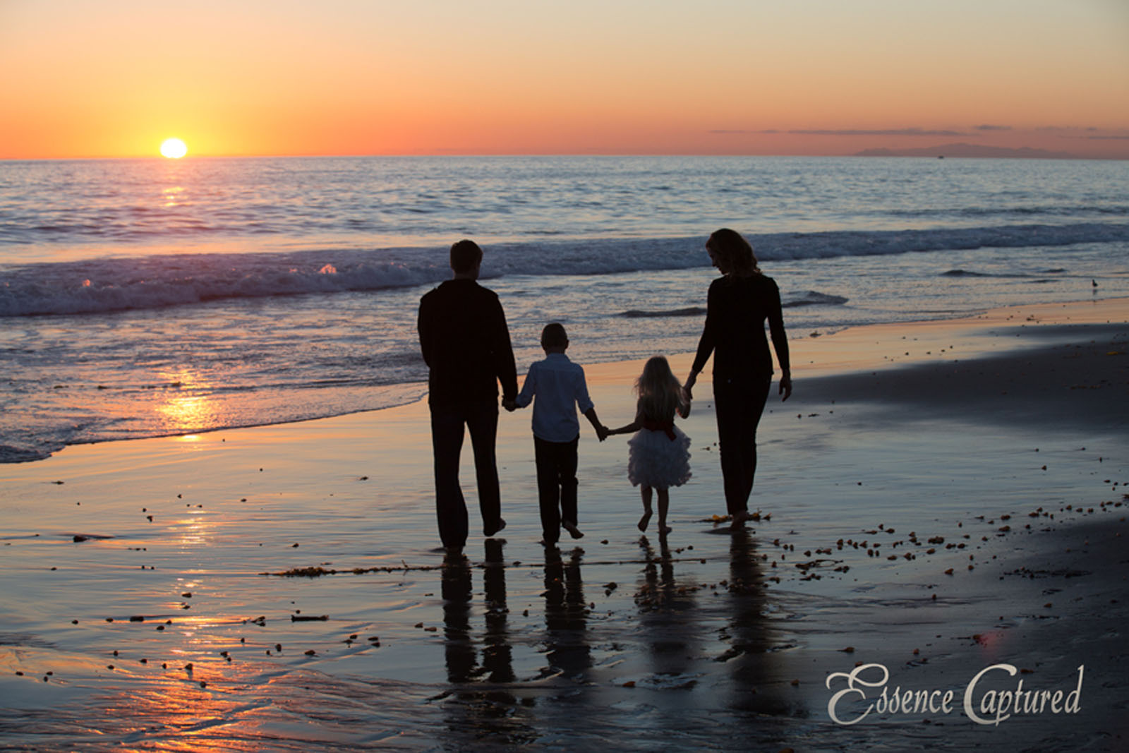 silhouette of family of four holding hands walking on beach at sunset